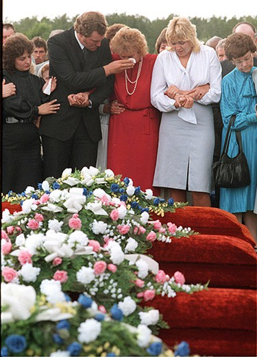 Arlene Reimer (in red) is comforted by relatives at the funeral of her husband and three children, Aug. 4, 1987.   ((Sun file photo))