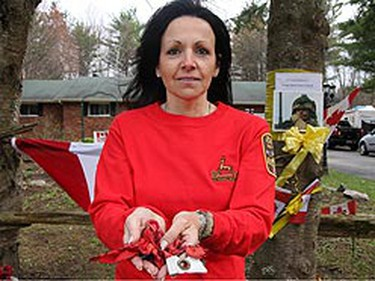 Darlene Cushman, mother of slain soldier Darryl Caswell, holds the remnants of the flag on her son's memorial that was burned. (TRACY McLAUGHLIN/Sun Media)