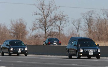 The hearse and limo carrying family members rides through Port Hope. A number of people, including veterans and emergency services workers, stand on the Hamilton Township Boundary road as the procession carrying the remains of Trooper Karine Blais passes by on April 16, 2009.  (PETE FISHER, Sun Media)