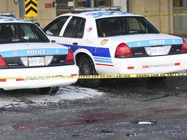 Images from the scene of this morning's murder of an Ottawa Police officer outside the emergency room doors at the Ottawa Hospital Civic Campus. Police cruisers sit outside the doors, with a pool of blood, a knife and an officer's gear scattered across the pavement. (ANDRE FORGET Sun Media)