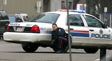 A police officer takes cover behind a police car after Edmonton police were called to a hostage situation at the Workers' Compensation Board building, 9912 - 107 St., Wednesday morning. David Bloom/Sun Media