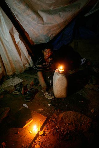 """Azharuddin Ismail, who acted in the film """"Slumdog Millionaire,"""" sits next to an oil lamp in his shack in Mumbai on Feb. 26, 2009. Ismail came back after attending the 81st Academy Awards. (REUTERS)"""