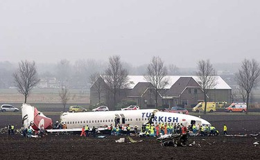 Emergency workers attend the scene where a Turkish Airlines passenger plane with 135 people aboard crashed while attempting to land at Amsterdam's Schiphol airport on Feb. 25, 2009. (REUTERS)