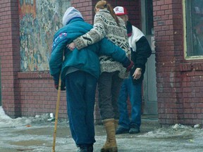 A Good Samaritan helps another lady on crutches cross the icy sidewalk outside the Salvation Army Booth Center on Main Street, as Winnipeg experiences another treacherous, icy day. (Marc Evans/FOR SUN MEDIA)