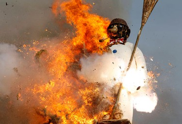 The Boeoegg, a snowman made of wadding and filled with firecrackers, explodes atop a bonfire in the Sechselaeuten square in Zurich April 11, 2011. REUTERS/Arnd Wiegmann