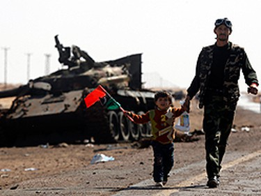 A rebel fighter escorts his son away from the front line at the western entrance of Ajdabiyah April 12, 2011. Forces loyal to Muammar Gadhafi bombarded the western entrance to the rebel-held town of Ajdabiyah in eastern Libya on Tuesday.   (REUTERS/Yannis Behrakis)