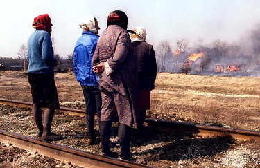 A group of women watch their burning houses in the abandoned village of Tovsty Lis near the Chernobyl nuclear power plant in this April 23, 1996 file photo.  REUTERS/Files