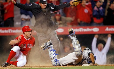 Los Angeles Angels' Peter Bourjos (L) slides by the tag of Toronto Blue Jays catcher J.P. Arencibia (R) to score the winning run on a basehit by Angels' Maicer Izturis (not pictured) during the fourteenth inning of their MLB American League baseball game in Anaheim, California on April 9, 2011. (REUTERS)