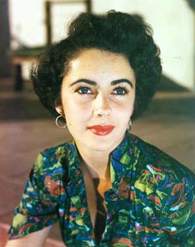 Look: Her uncommon and beautiful violet blue eyes were set off by greens and blues, like this printed blouse she wore in the '50s.  (WENN.COM)