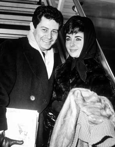 Year: 1959.  Look: Though her complexion was quite fair at the time, Taylor's raven hair allowed her to wear dark clothes and accessories without looking washed out. Above, she keeps her hair-do in place under a chic scarf while out with then-husband Fisher.   (WENN.COM)