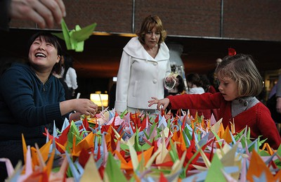 Helper fold paper cranes during a origami session called Senbazuru (A thousand cranes) in favour of disaster victims in Japan in the Ahondiga cultural centre in Bilbao March 26, 2011. An ancient Japanese legend states that a crane will grant a wish to the maker of a thousand origami cranes. The Japanese government on Wednesday estimated the direct damage from a deadly earthquake and tsunami that struck the country's northeast this month at as much as $310 billion US, making it the world's costliest natural disaster. REUTERS/Vincent West