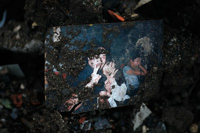 A photograph is seen in the rubble of a destroyed house in Otsuchi, after the area was devastated by a magnitude 9.0 earthquake and tsunami, March 22, 2011. REUTERS/Damir Sagolj