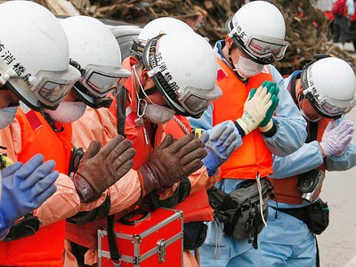 Rescue workers pray over a body recovered from wreckage from an earthquake and tsunami in Rikuzentaka, Iwate Prefecture, northeastern Japan, in this picture taken by Kyodo News on March 21, 2011. (REUTERS/Kyodo)