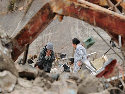 A woman reacts in front of her destroyed house in Onagawa City, Miyagi Prefecture, in this picture taken by Kyodo News on March 20, 2011. The area was devastated by a magnitude 9.0 earthquake and tsunami on March 11. (Mandatory Credit REUTERS/Kyodo)