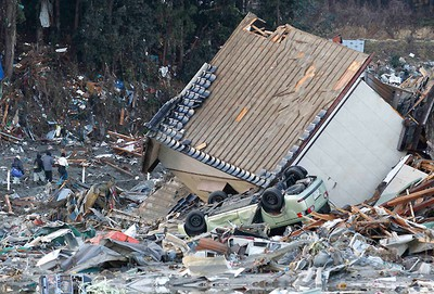 People walk past a destroyed house in Minamisanriku Town, Miyagi Prefecture in northern Japan, March 16, 2011, days after the area was devastated by a magnitude 9.0 earthquake and tsunami.  REUTERS/Kim Kyung-Hoon