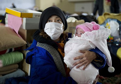 A mother holds her baby at the Yonezawa gymnasium, in Yamagata prefecture March 25, 2011. Japan is grappling with a three-sided disaster -- a March 11 earthquake registering a magnitude of 9.0, subsequent tsunamis and attempts to stabilize the damaged nuclear power station. (Christian Aslund/Greenpeace/HO)