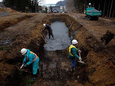 Workers prepare a mass grave for the funeral of victims of the earthquake and tsunami in Kamaishi, Iwate Prefecture March 26, 2011. The March 11 quake and tsunami have left at least 27,000 dead and missing in northeast Japan. (REUTERS/Damir Sagolj)