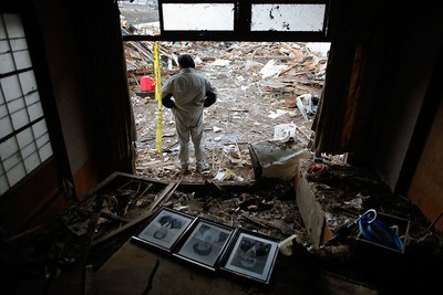 Katsuyuki Takahashi stands behind the portraits of his parents and aunt that he recovered from a destroyed family house in Kesennuma, Miyagi Prefecture, after the area was devastated by a magnitude 9.0 earthquake and tsunami March 31, 2011.   REUTERS/Damir Sagolj
