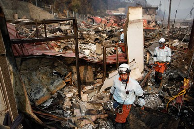 Japanese rescue workers search through rubble in a residential area of tsunami-hit Otsuchi March 14, 2011. In the town of Otsuchi in Iwate prefecture, 12,000 out of a population of 15,000 have disappeared following Friday's massive earthquake and tsunami. REUTERS/Damir Sagolj
