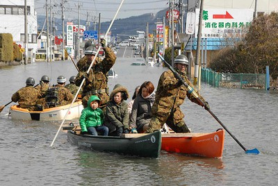 Self-Defence Force officers rescue people by a boat after a tsunami and earthquake in Ishinomaki City in Miyagi Prefecture on March 12, 2011. (REUTERS/Yomiuri)