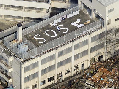"""People wait to be rescued atop a building with the letters """"SOS"""" after an earthquake in Kesennuma, Miyagi Prefecture March 12, 2011. (Reuters)"""