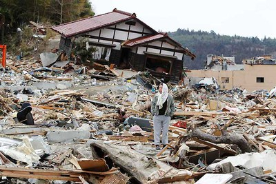 A man looks at his village destroyed by the earthquake and tsunami in Rikuzentakata in Iwate prefecture, northeast Japan March 15, 2011.   REUTERS/Toru Hanai