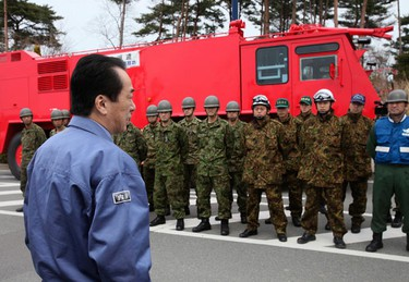 Japan's Prime Minister Naoto Kan (L), dressed in the blue work clothes, speaks to members of the Japan Ground Self-Defense Force as he visits J-village, about 20 km (12 miles) from the Tokyo Electric Power Co.'s Fukushima Daiichi Nuclear Power Plant, at Naraha town in Fukushima prefecture. REUTERS/Prime Minister's Office of Japan/Handout