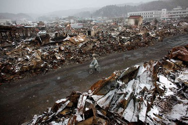 An emergency worker cycles past debris in Yamada, Iwate Prefecture, days after the area was devastated by a magnitude 9.0 earthquake and tsunami, March 17, 2011. REUTERS/Aly Song