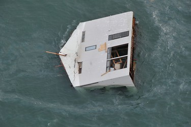 Seen from an HH-60G helicopter, a house drifts in the ocean east of Sendai, in this U.S. Air Force handout photo dated March 14, 2011. REUTERS/US Air Force/Airman 1st Class Katrina R. Menchaca/Handout