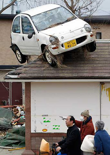 A car is seen on the rooftop of a house as South Korean rescue workers walk past it in an area hit by an earthquake and tsunami in Sendai, northeastern Japan March 15, 2011.  REUTERS/Jo Yong-Hak