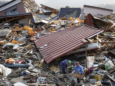 People salvage possessions from the rubble in Rikuzentakata, northern Japan after the magnitude 8.9 earthquake and tsunami struck the area, March 13, 2011. Japan faced a growing humanitarian crisis on Sunday after its devastating earthquake and tsunami left millions of people without water, electricity, homes or heat.   REUTERS/Lee Jae-Won
