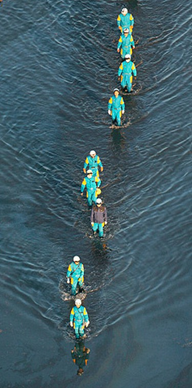 A rescue team searches for missing people in Sendai, northeastern Japan on March 12, 2011. (REUTERS/Kyodo)