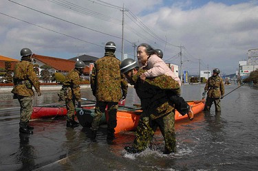 Self-Defence Force officers rescue a woman by a boat after a tsunami and earthquake in Ishinomaki City in Miyagi Prefecture on March 12, 2011. (REUTERS/Yomiuri)