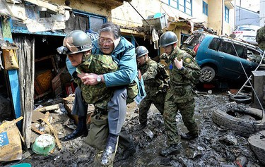 A man who was trapped by a tsunami is rescued by a Japan Self-Defence Force soldier in Kesennuma City in Miyagi Prefecture in northeastern Japan on March 12, 2011. (REUTERS/Kyodo)