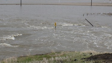 A highway sign is half submerged west of Brandon. Water had completely washed over the Grand Valley Road turnoff by May 12, 2011. (Jillian Austin/Winnipeg Sun)