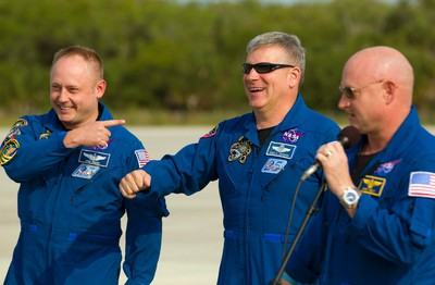 The space shuttle Endeavour STS-134 pilot Gregory Johnson (C) laughs after it was pointed out today is his birthday while arriving with mission specialist Michael Fincke and commander Mark Kelly (R) at the Kennedy Space Center in Cape Canaveral, Florida May 12, 2011. REUTERS/Scott Audette