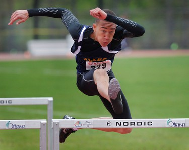 John Bailey from Glebe C.I. stays low as he competes in the junior men's 100-m hurdles Wednesday. The National Capital Track and Field Championships took place at the Terry Fox Field Wednesday May 18.  TONY CALDWELL/OTTAWA SUN