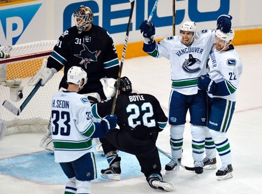 Vancouver Canucks Alex Burrows (2nd R) celebrates his goal against the San Jose Sharks goalie Antti Niemi (2nd L) with team mates Daniel  and Henrik Sedin (L) during the third period of Game 4 in their NHL Western Conference Final hockey playoff game in San Jose, California, on May 22, 2011. (REUTERS)
