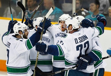 Members of the Vancouver Canucks including Ryan Kesler, Daniel Sedin and Henrik Sedin (C) celebrate the second goal scored by Sami Salo against the San Jose Sharks during the second period of Game 4 in their NHL Western Conference Final hockey playoff game in San Jose, California, on May 22, 2011. (REUTERS)