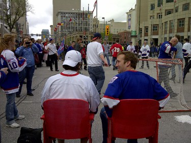 Winnipeg Jets fans watch a road hockey game at Portage and Main following the press conference announcing the return of the NHL. (BERNICE PONTANILLA/Winnipeg Sun)