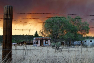 House are seen along the U.S. Route 180 as smoke from the Wallow Wildfire fills the sky in Luna, New Mexico June 6, 2011. REUTERS/Joshua Lott