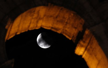 A shadow falls on the moon during a lunar eclipse at the ancient Colosseum in Rome on June 15, 2011. (REUTERS/Alessandro Bianchi)