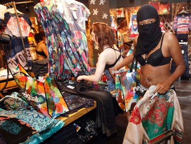 Shoppers in their underwear search for items at a clothing store in London June 16, 2011. Spanish fashion brand Desigual started a special sale in London on Thursday, by offering the first 100 customers two clothes for free as long as shoppers arrived at the store dressed only in their underwear.   REUTERS/Luke MacGregor