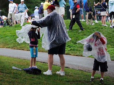 Spectators put on rain gear as rain falls during first round play at the 2011 U.S. Open at Congressional Country Club in Bethesda, Maryland, Thursday, June 16, 2011. (REUTERS/Jonathan Ernst)