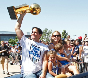 Dallas Mavericks owner Mark Cuban holds the championship trophy as he rides in a car with his family during a parade to celebrate their NBA championship in Dallas, Texas June 16, 2011.  Dallas defeated the Miami Heat to win the 2011 NBA title. (REUTERS)