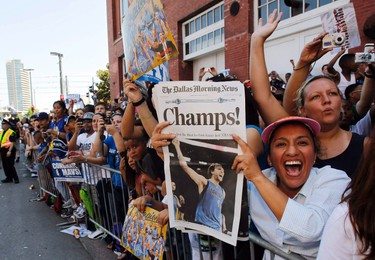 Mary Munoz of Dallas holds a newspaper with a picture of Dallas Mavericks forward Dirk Nowitzki as she watches a parade to celebrate their NBA championship in Dallas, Texas June 16, 2011.  Dallas defeated the Miami Heat to win the 2011 NBA title. (REUTERS)