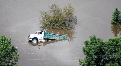 A dump truck is seen in flood waters in Sawyer, North Dakota, near the Souris River June 25, 2011. Flood projections forecast about 18 more inches (46 cm) of water before levels begin dropping. (REUTERS/Allen Fredrickson)