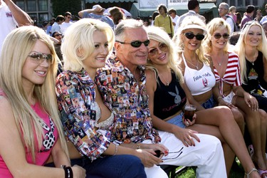 Playboy Magazine founder Hugh Hefner is joined by models for a Sugar Ray Leonard Boxing event at the Playboy Mansion in Beverly Hills, California July 9, 2002. From left, are; Renee Sloan, Holly Madison, Hefner, Tiffany Holliday, Stacey Burke, Bridget Marquardt and Isabella Kaspryk. REUTERS/Robert Galbraith