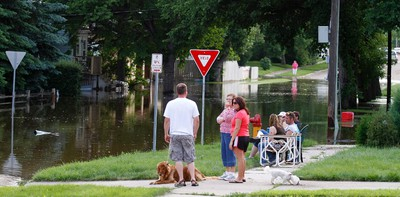 Residents watch the level of water rise in the streets of Minot, North Dakota June 24, 2011, as flood waters from the Souris River spills over levees and dikes. REUTERS/Allen Fredrickson