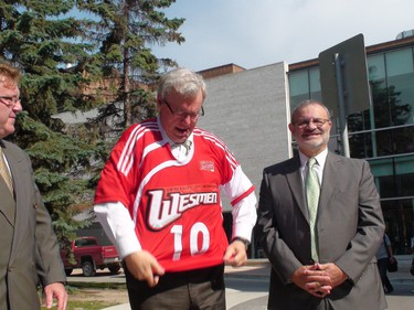 Premier Greg Selinger tries on a University of Winnipeg Wesmen soccer jersey given to him as a gift during a press conference June 30, 2011 for the U of W's new fieldhouse, as David Fitzpatrick, the U of W's dean of arts, looks on. The province and university are jointly funding the $35 million project. (PAUL TURENNE/Winnipeg Sun)